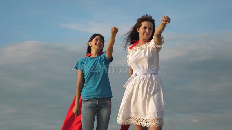 Παιχνίδι Mom και κορών superheroes σε έναν κόκκινο επενδύτη ευτυχή οικογενειακά παιχνίδια έξοχοι ήρωες Η μητέρα και το παιδί βάζο στοκ εικόνες