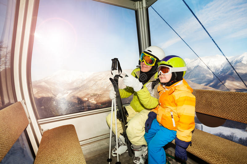 Mom talk to child sitting in ski lift cabin. Mother and little boy son skier sit in cable car cabin on ski resort with mother pointing finger and explaining royalty free stock photo