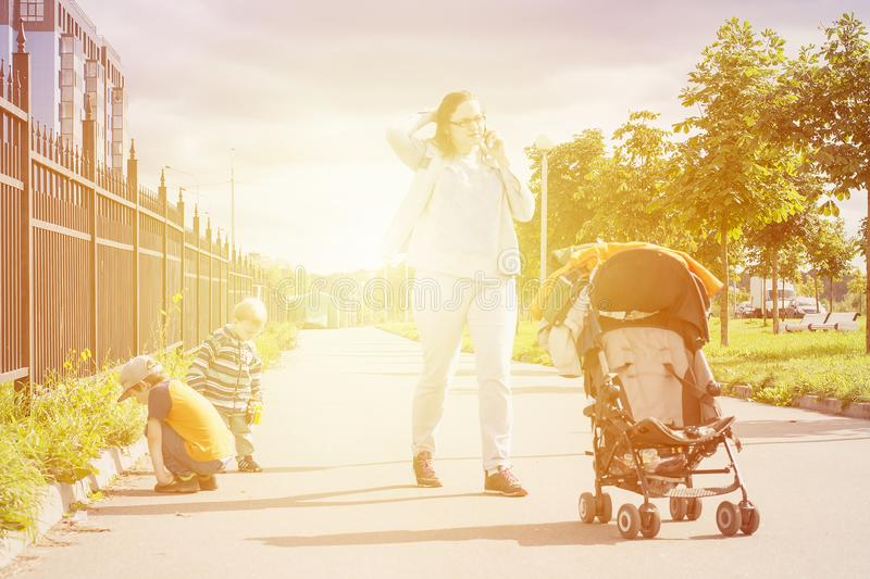 Mom talking by phone during outdoor walk with kids. royalty free stock photography