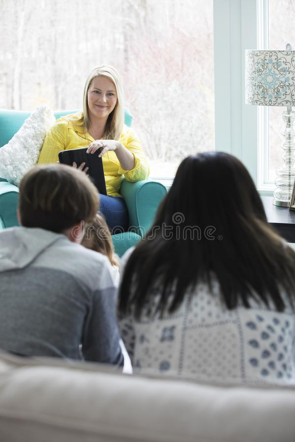 Family at Home. A mom talking to her kids in a bright, modern living room royalty free stock photo