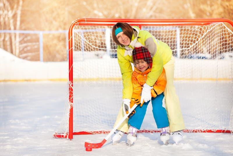 Mom teach boy to play ice hockey. Mother teach little son to play ice hockey and hold hockey stick standing near gates on ice stock image
