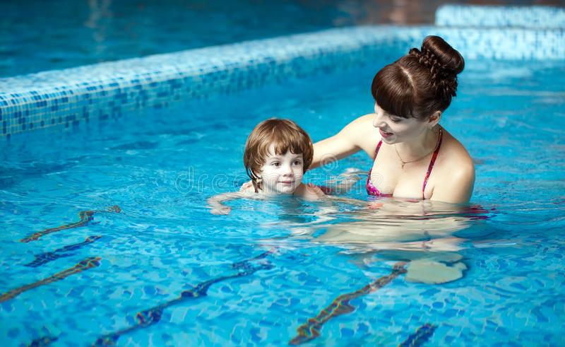 Mom teaches a child to swim in the pool.  stock photo