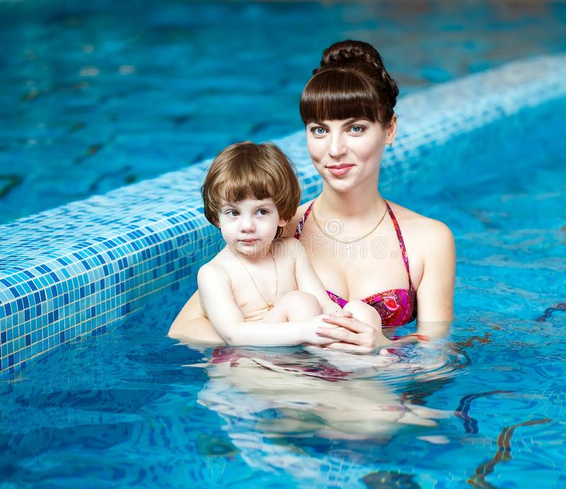 Mom teaches a child to swim in the pool.  royalty free stock photography