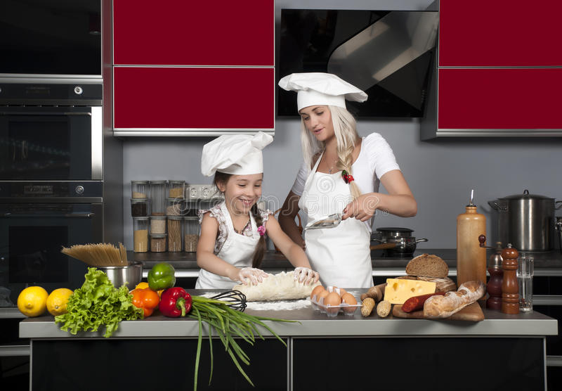 Mom teaches daughter to cook stock photos
