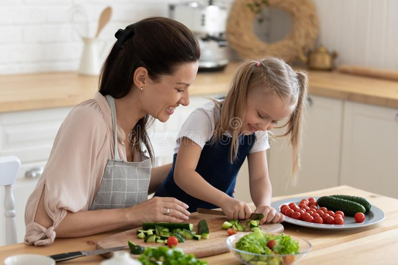 Mom teaches daughter to cook vegetable salad stock images