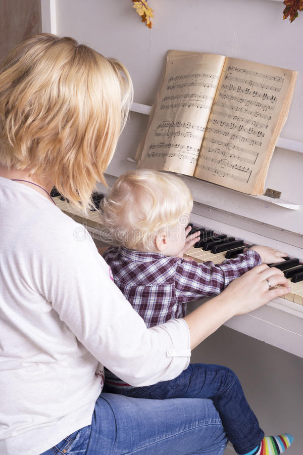 Mom teaches a little child to play the piano stock images