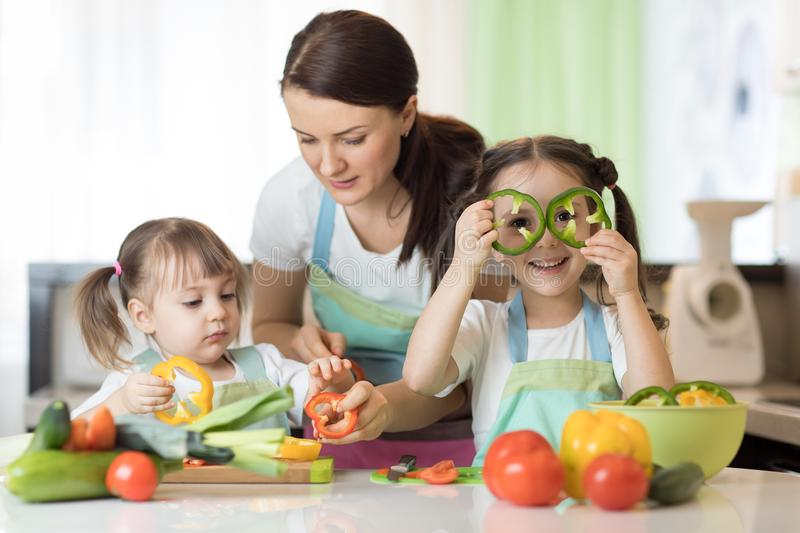 Mom teaches two daughters to cook at the kitchen table with raw food royalty free stock photos