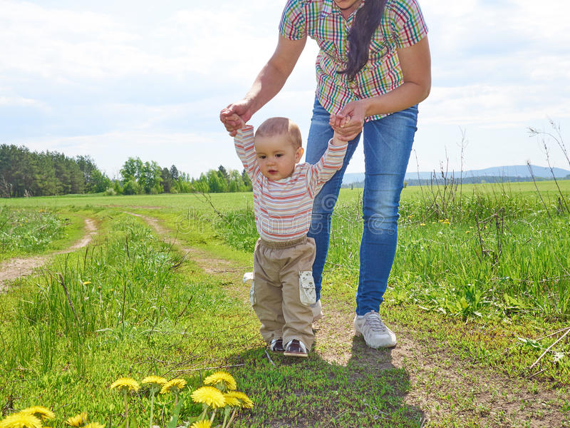 Mom teaches walks young son. stock image