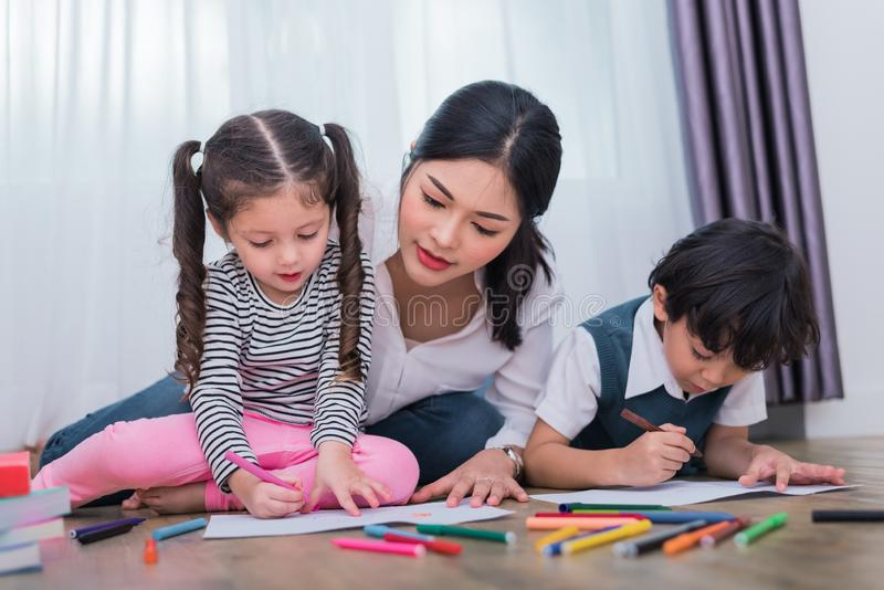 Mom teaching children in drawing class. Daughter and son painting with colorful crayon color in home. Teacher training students in. Art classroom. Education and stock photo
