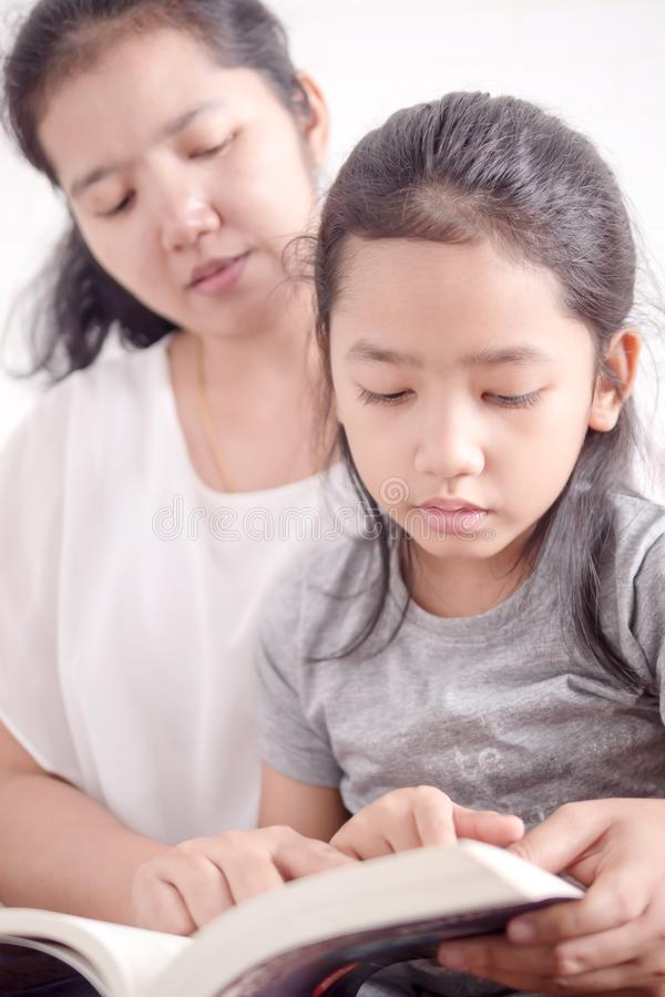 Mom teaching daughter to reading a book royalty free stock image