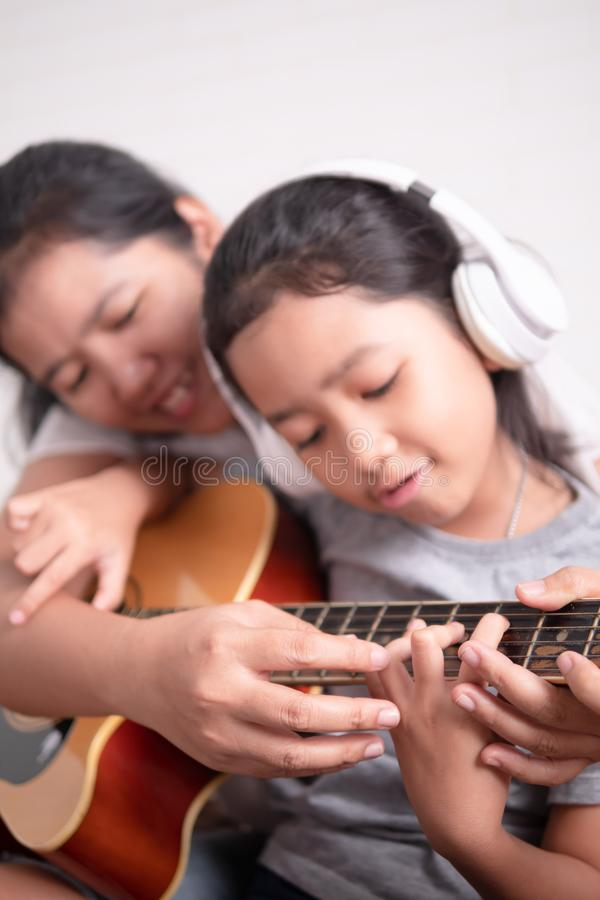 Asian little girl learning to play music. Mom is teaching her daughter to play guitar. Asian little girl learning to play music. Children wear a white headphone stock images