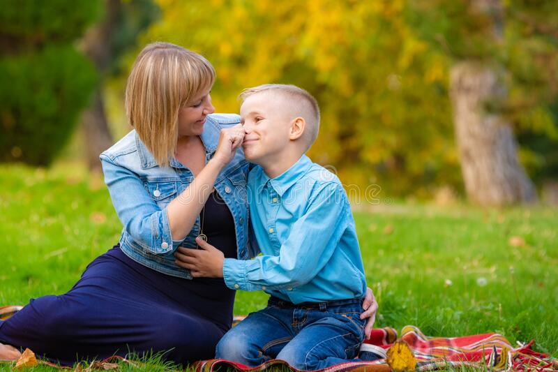 Mom tenderly took her teen`s nose while relaxing in a clearing in a park stock photography
