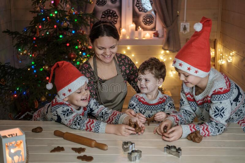 mom and three sons make ginger cookies for Christmas royalty free stock image