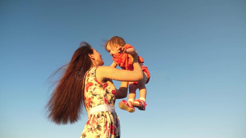Mom throws her daughter up to the sky. mother plays with a small child against a blue sky. happy family playing in the stock images