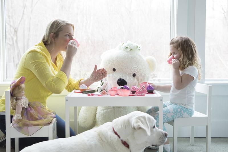 A mom and toddler having a tea party. A little girl having a pretend tea party with her mom.Her teddy bear and dog look on stock photos