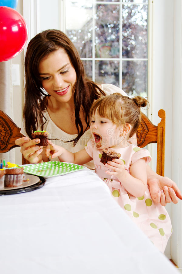 Mom and toddler share cupcake experience royalty free stock image