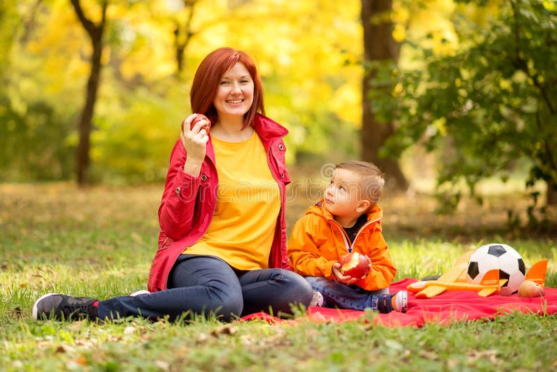 Mom and toddler son on autumn picnic in park or forest. Healthy parenting and active family leisure outdoors concept royalty free stock photos
