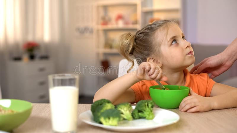 Mom touching girl who eating healthy breakfast, vegetarian lifestyle, broccoli royalty free stock image