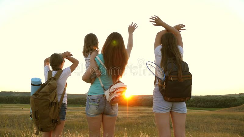 Mom travels with her daughters, admire the sunset and wave their hands. Mom and children are tourists. girls travel in royalty free stock photos