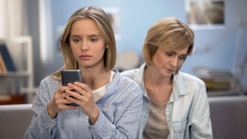 Mom trying to talk to teenage child at home, relations problem, phone addiction stock photos