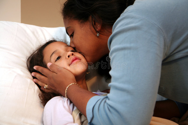 Mom Tucking Child into Bed royalty free stock photo