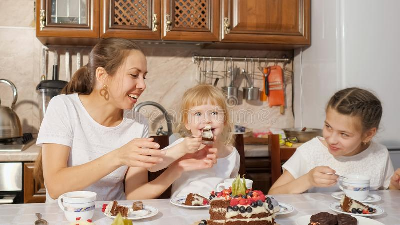 Mom and two daughters are having a tea with homemade chocolate cake in the kitchen, family birthday at home. royalty free stock photos