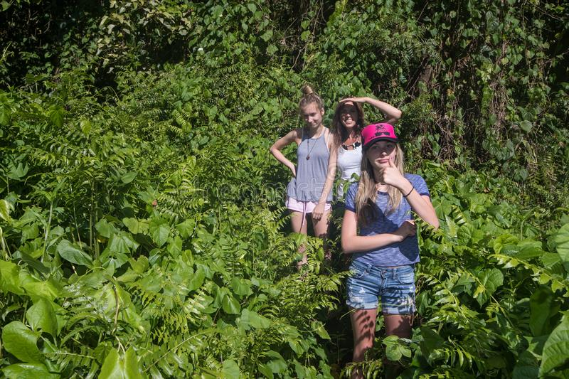 Mom and two daughters hiking in a jungle stock photography