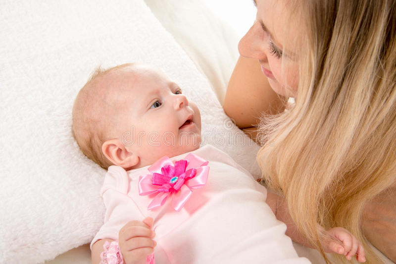 Mom and two-month baby looking at each other. A two-month baby lying on his back on the bed, sitting next to the child and mother looking at her royalty free stock images