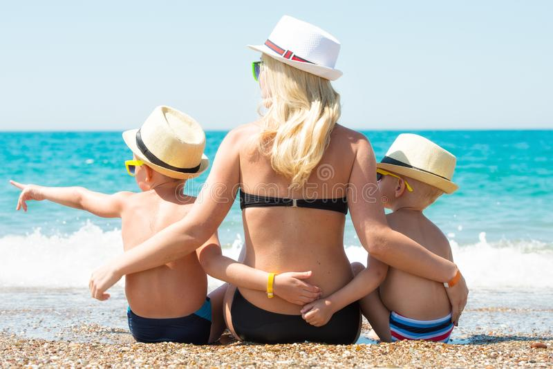 Mom and two sons in hats sitting on the beach and looking at the sea. royalty free stock photo