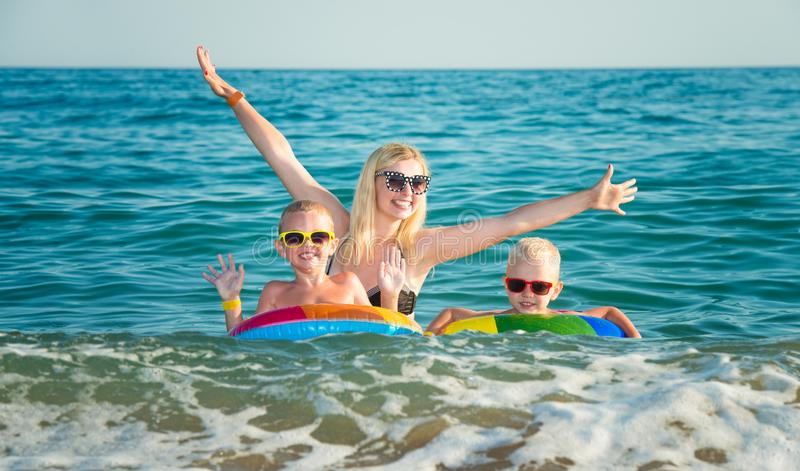 Mom and two sons are swimming in the sea. Children in bright inflatable circles. Summer vacations. Summer vacations.Mom and two sons are swimming in the sea royalty free stock photography