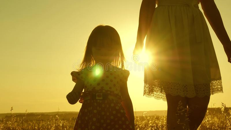 Mom walks across the field with a small child at sunset. daughter holds mom`s hand, a happy family walks in evening out royalty free stock photo