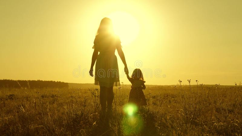Mom walks on field with her little daughter in sunset. baby holds mom`s hand, a happy family walks in evening out of royalty free stock photography