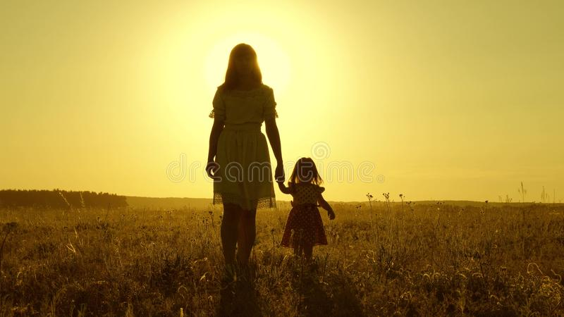 Mom walks on field with her little daughter in sunset. baby holds mom`s hand, a happy family walks in evening out of stock image