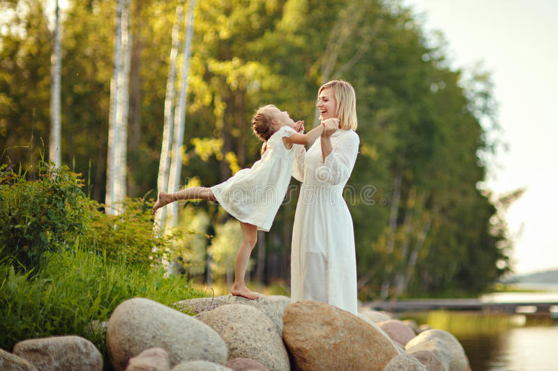 Mom in a white dress with her daughter sitting on large rocks on stock images