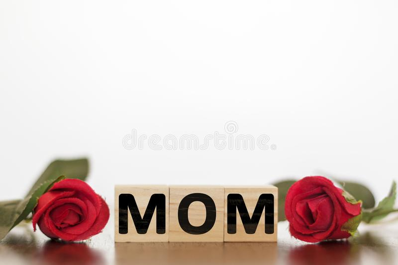 MOM word written on wooden cubes with red roses around. Mothers day concept. MOM word written on wooden cubes with red roses around. Mother`s day concept royalty free stock images