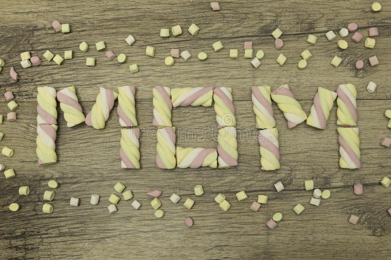 MOM written with marshmallows. Mother`s day concept. Spring holidays. On wooden background. royalty free stock photos