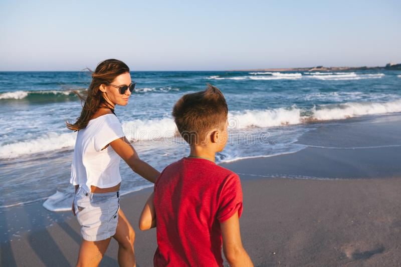 Mom and son walking and playing on the beach royalty free stock photography