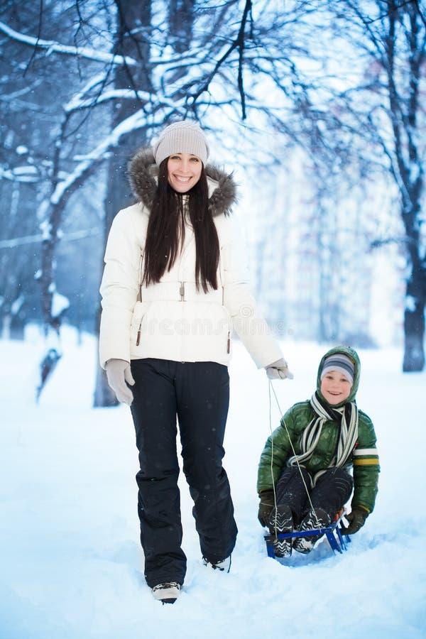 Momen är rullande henne sonen på en sled arkivfoto
