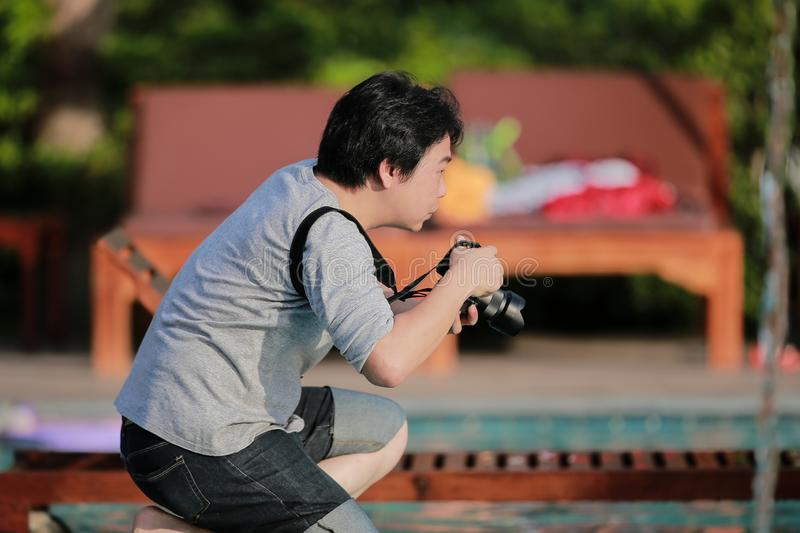The moment of Asian Thai Professional photographer is kneeling and wating for take a great photo. The moment of Asian Thai Professional photographer is kneeling stock photo