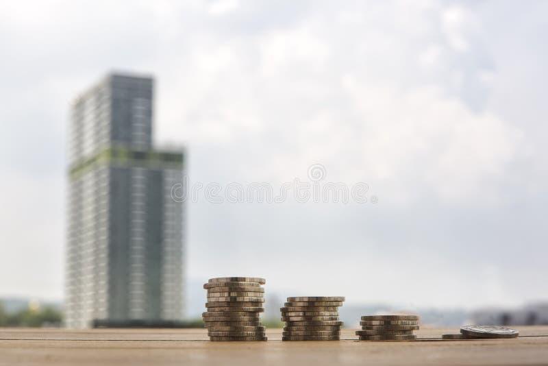 Moment av myntbuntar, guld- mynt på suddig byggnadsbakgrund arkivbilder