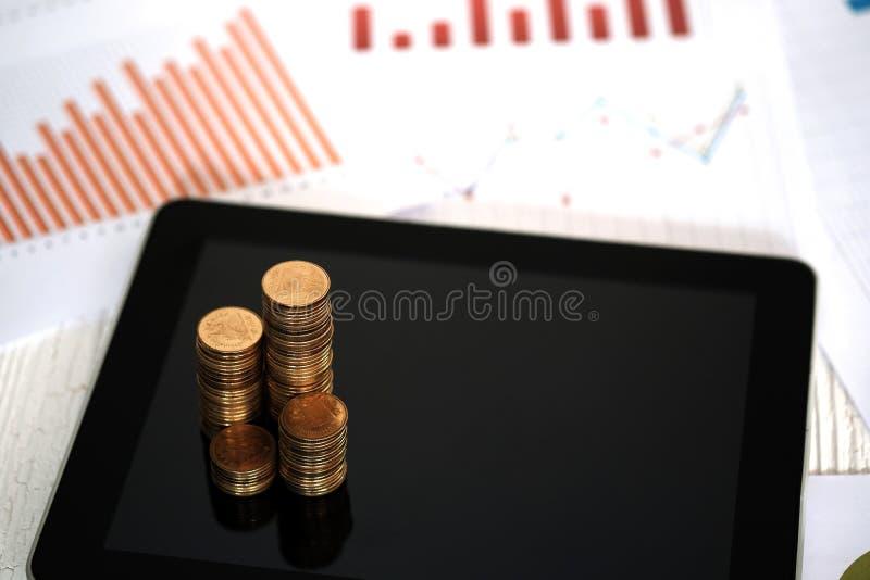 Moment av myntbuntar och minnestavladatoren med den finansiella grafen, vision för affärsplanläggning och finansanalys arkivbilder