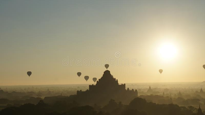 The moment of breaking dawn with balloons. The moment of breaking dawn with horizon and very small flying balloon together new sunlight of the day on the haze stock image