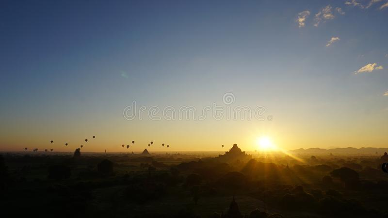 The moment of breaking dawn with balloons. The moment of breaking dawn with orange blue horizon and very small flying balloon together new sunlight of the day on stock photo