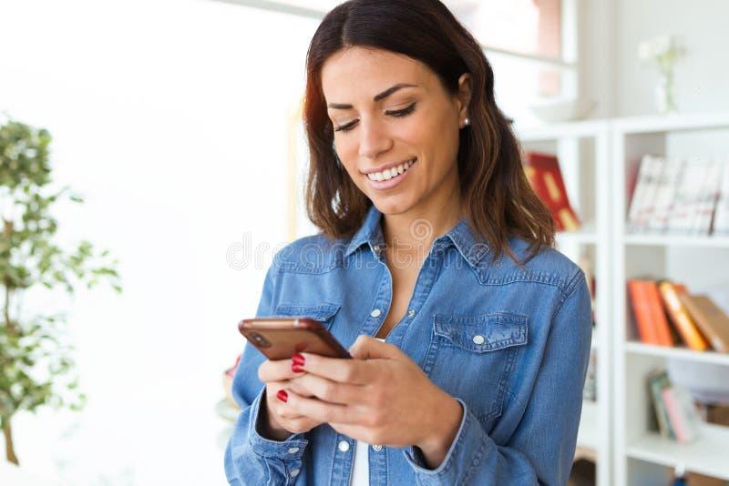 Moment de sourire de jolie jeune femme utilisant son téléphone portable sur le salon à la maison image stock