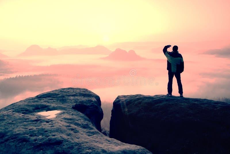 Moment der Einsamkeit Mann auf den Felsenreichen und Uhr über dem nebelhaften und nebeligen Morgental zu Sun stockfoto