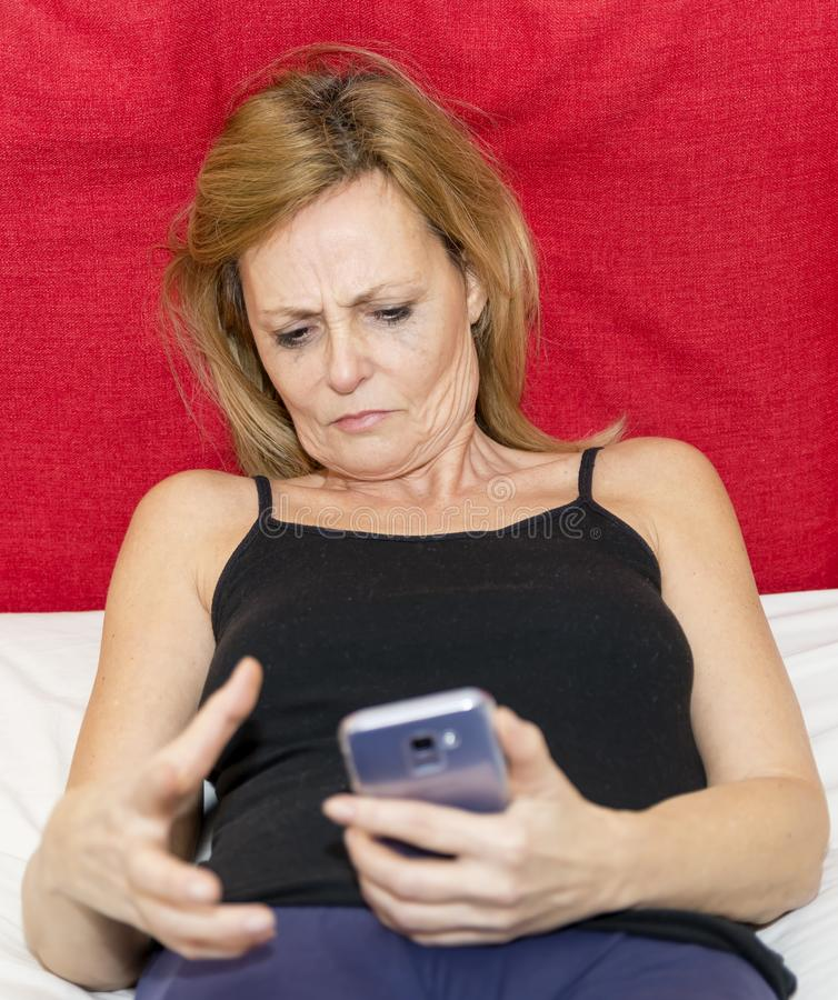 Moment of despair of a woman who is looking at the display of her smartphone royalty free stock photography