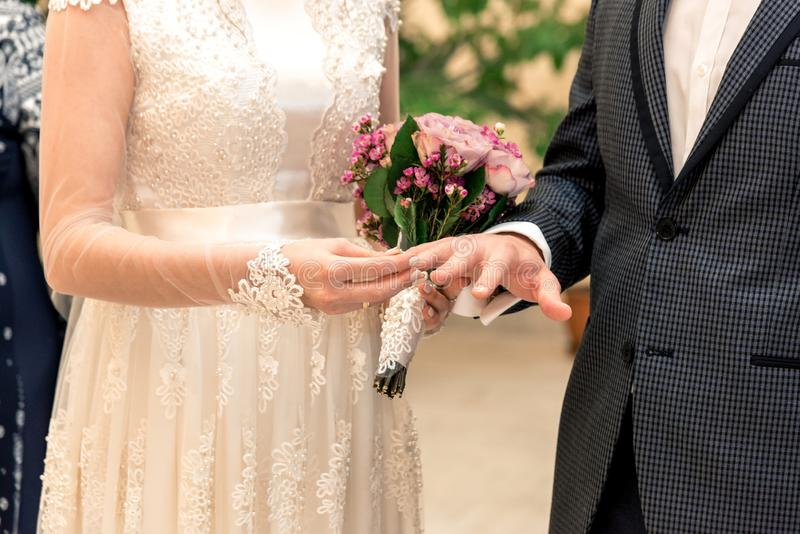 The moment of the exchange of the rings of the newlyweds, the bride puts a ring on the hand of the groom royalty free stock images