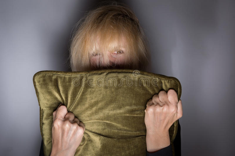 Moment of Fear. Mentally ill woman hiding in fear behind pillow royalty free stock photo