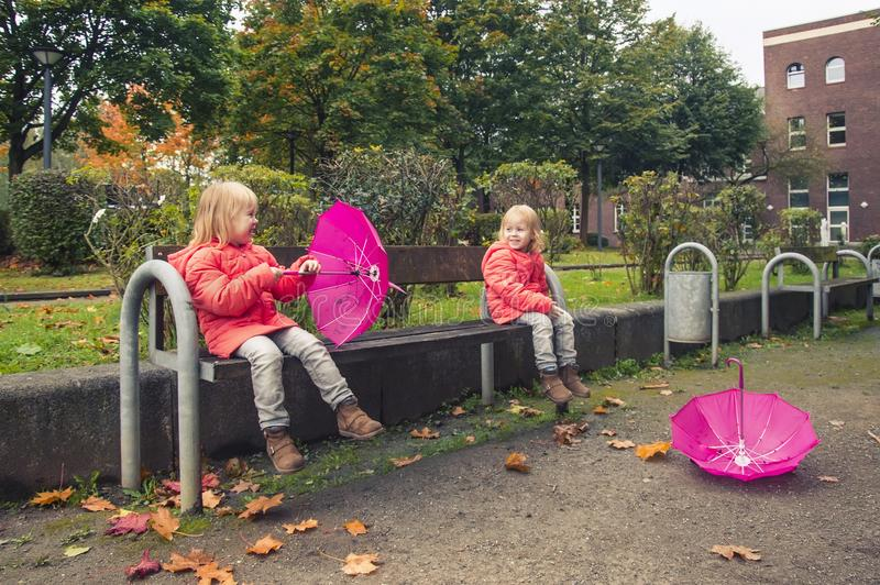 Moment of happiness! Happy little girls with umbrellas on a sunny autumn day after the rain, children in bright jackets in the par royalty free stock photography