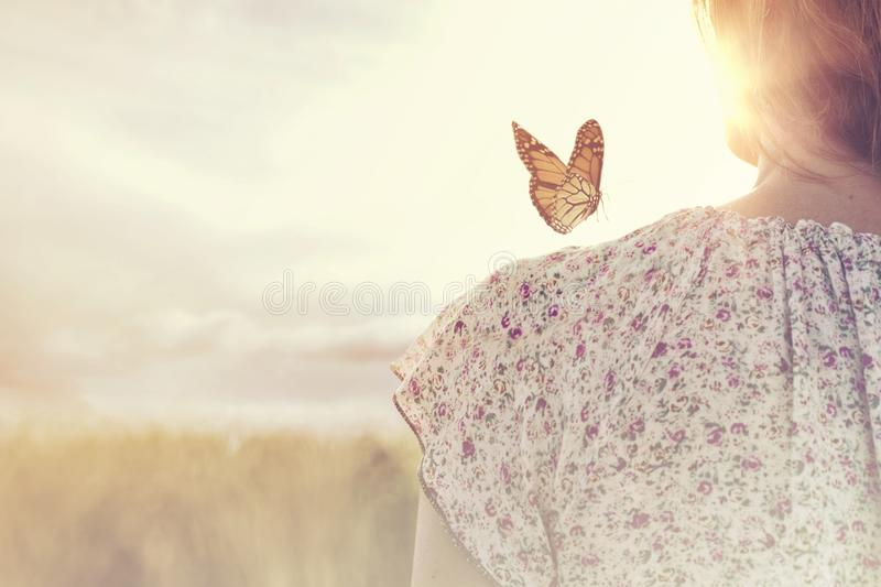 moment of meeting between a butterfly and a girl in the middle of nature stock photography